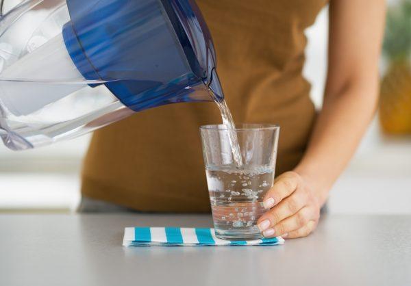 Женщина наливает воду в стакан