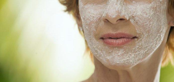 Женщина в морщинах с белой маской на лице