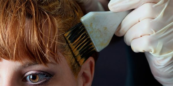Женщина красит волосы хной
