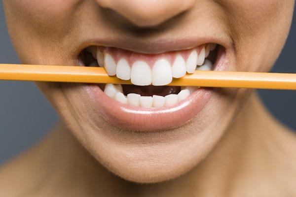 Девушка держит карандаш между зубами
