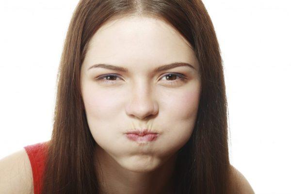 Девушка с надутыми щеками