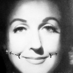 Женщина улыбается, раздвигая губы