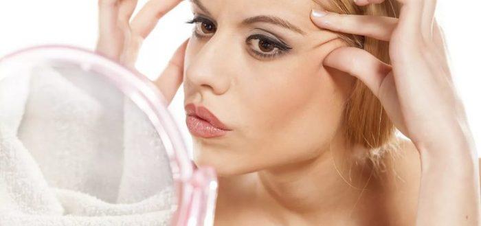 Женщина рассматривает своё лицо в зеркале