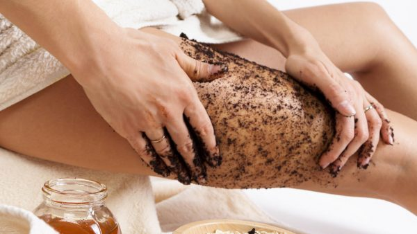Девушка скрабирует кожу ног