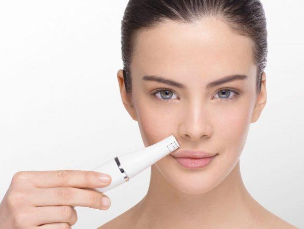 Девушка использует эпилятор для удаления волос на лице