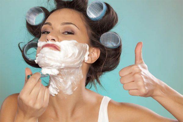 Девушка с бигуди на волосах бреется