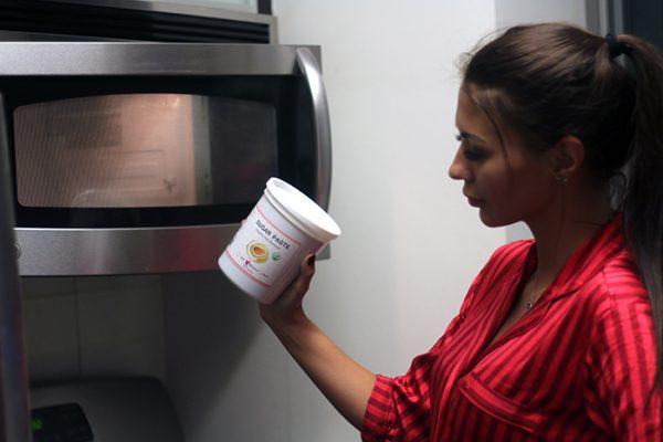 Девушка ставит ёмкость с сахарной пастой в микроволновку
