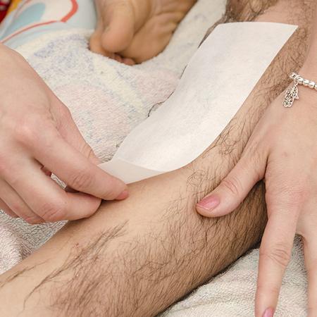 Процедура восковой депиляции на ноге