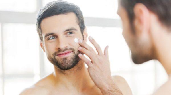 Мужчина перед зеркалом наносит на лицо крем