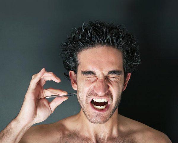 Мужчина выдергивает пинцетом волос из бороды