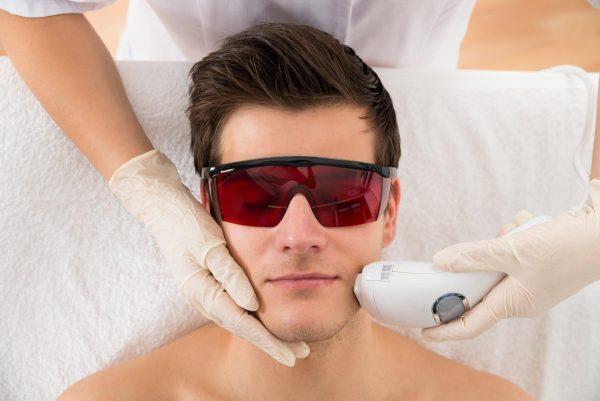 Мужчина в защитных очках на процедуре лазерной эпиляции лица