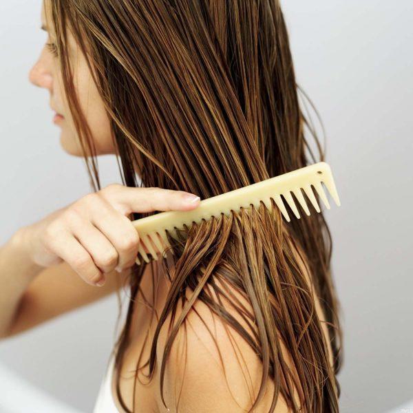 Девушка расчёсывает влажные волосы