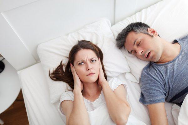 Сцена в постели: женщина зажала уши, муж храпит