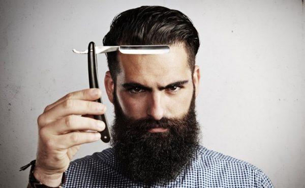 Мужчина с бородой и бритвой в руке