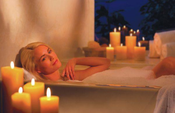 Девушка принимает ванну и свечи вокруг