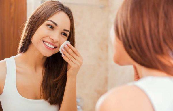 Девушка протирает лицо ватным диском перед зеркалом