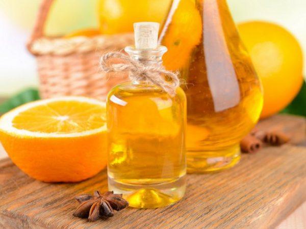 Эфир апельсина в прозрачной бутылке и плоды