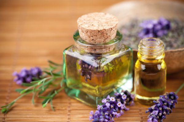 Эфирные масла и ветки лаванды на столе