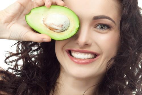 Улабающаяся женщина держит половинку авокадо