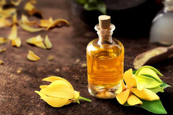 Масло иланг-иланга в прозрачном флаконе и цветы