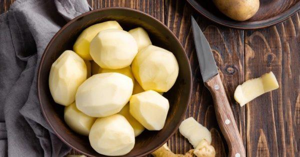 Сырой очищенный картофель в тарелке