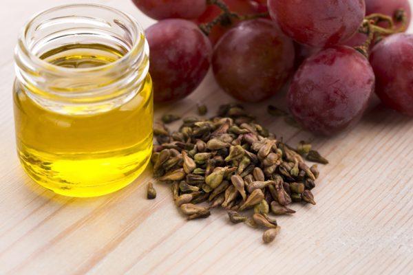 виноградное масло в стеклянной баночке, гроздь винограда и виноградные косточки