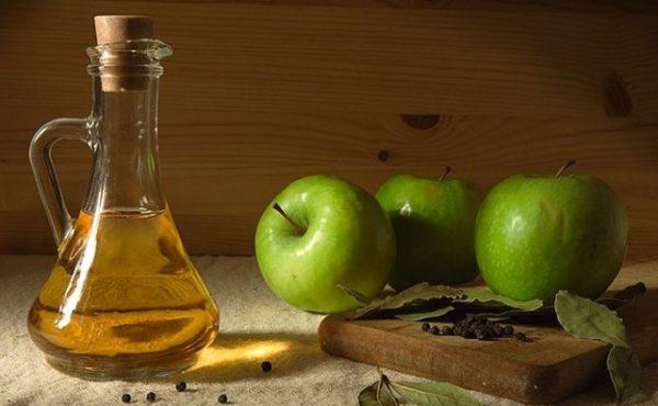 Яблочный уксус в прозрачном сосуде и плоды