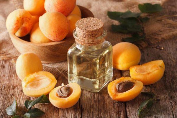 Абрикосовое масло в прозрачном флаконе и плоды