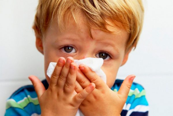 Ребёнок с салфеткой у лица