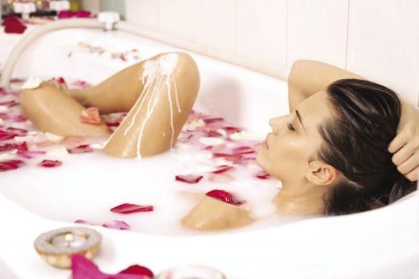 Девушка лежит в ванне с лепестками роз