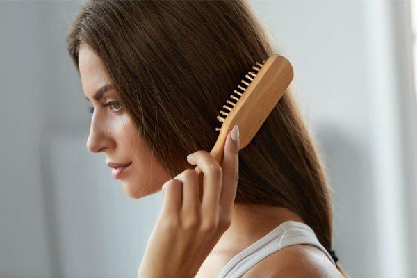 Девушка расчёсывает волосы деревянной расчёской