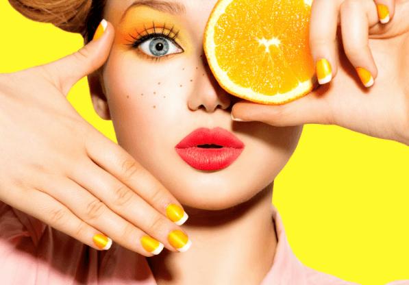 Девушка с веснушками и апельсином у лица