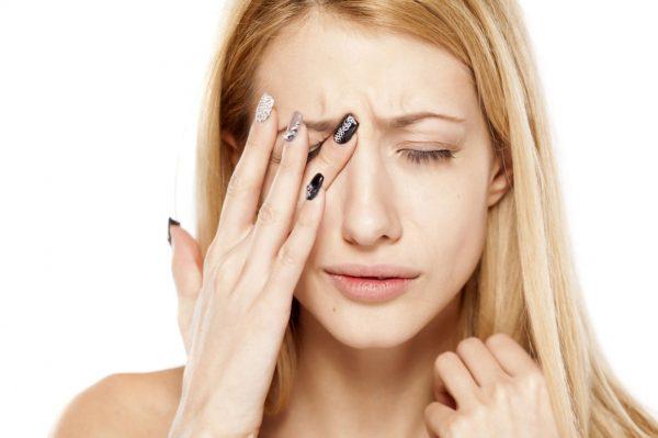 Девушка закрывает глаз рукой