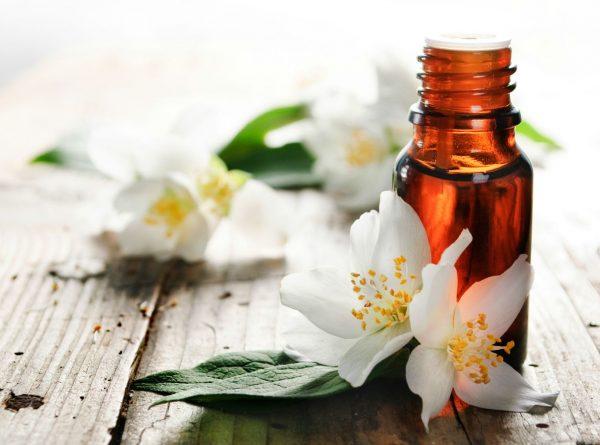 Эфирное масло нероли в тёмном флаконе и цветы