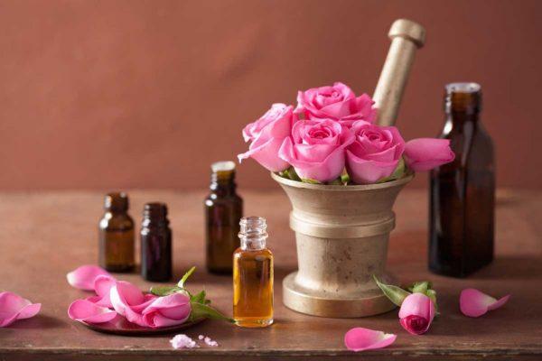 Эфирное масло розы в прозрачной бутылочке и цветы