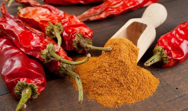 Красный молотый перец на деревянной лопаточке