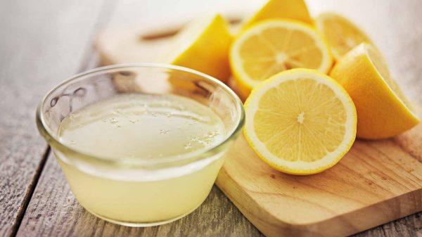 Лимонный сок в прозрачной пиале и фрукты в разрезе