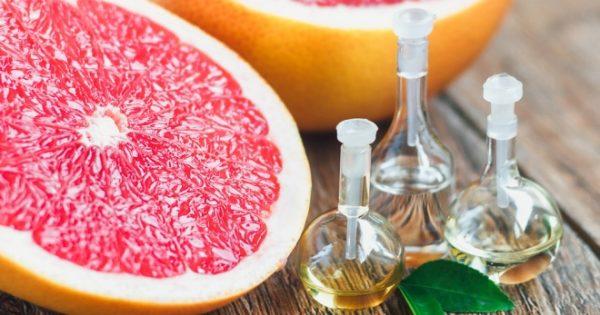 Масло грейпфрута в прозрачных флаконах и плоды в разрезе