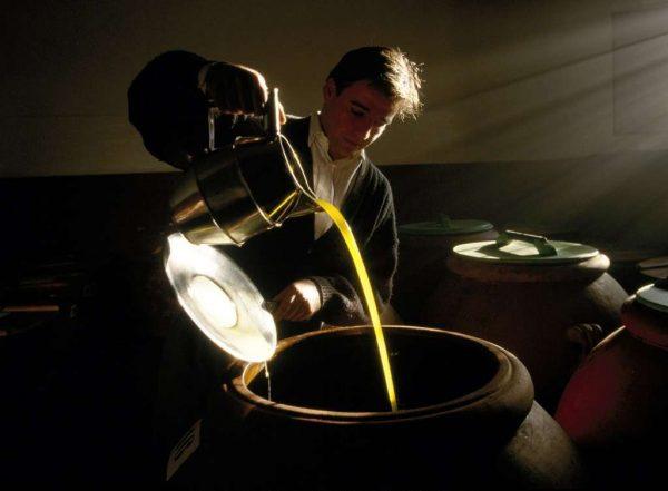 Переливание оливкового масла в бочку