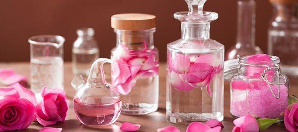 Розовая вода в прозрачных флаконах и лепестки роз