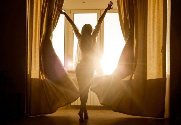 Девушка открыла шторы утром