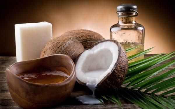 Кокосовое масло в прозрачном флаконе и плоды в разрезе