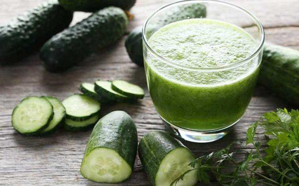 Огуречный сок в прозрачной ёмкости и овощи