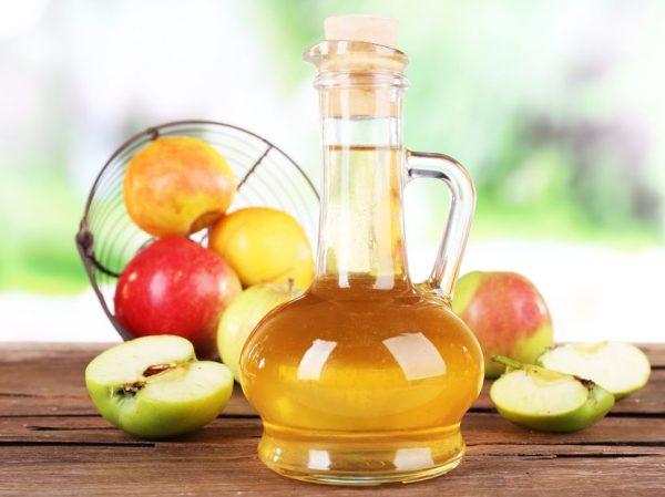 Яблочный уксус в прозрачном графине и фрукты