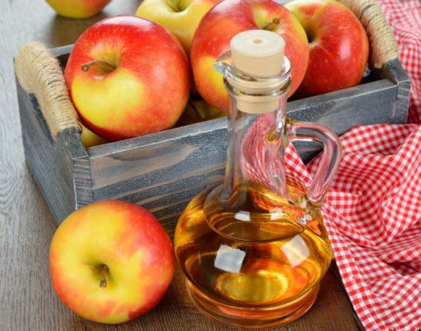 Яблочный уксус и яблоки на столе