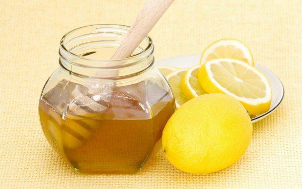 Мёд в прозрачной банке, порезанный лимон на тарелке
