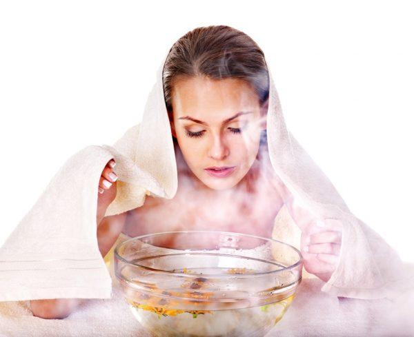 Женщина, укрытая полотенцем, смотрит на прозрачную ёмкость с кипятком