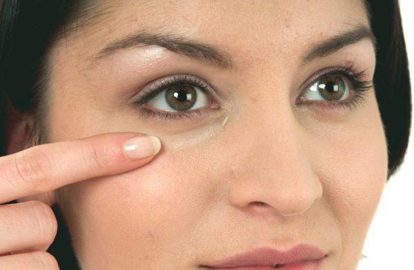 Женщина размазывает мазь под глазом