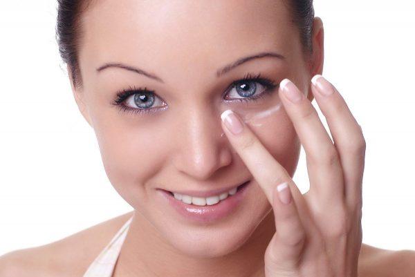 Девушка наносит крем под глаза
