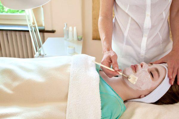 Косметолог наносит на лицо лежащей на кушетке женщины белую маску при помощи кисти